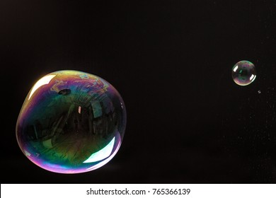 Photographed soap bubbles, one giant and one small on black background.