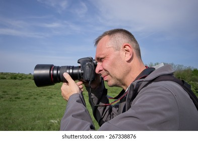 Photographer in action with backpack in nature