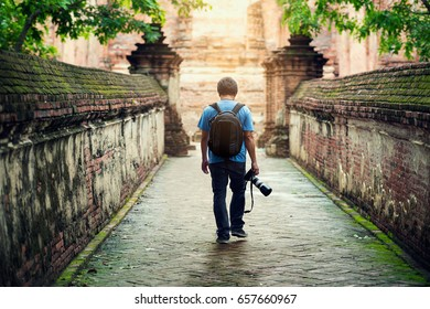 Photographer backpacker tourist man walk and take a photo by camera Professional in Asia Thailand Ayutthaya wat maheyong famous temple.
