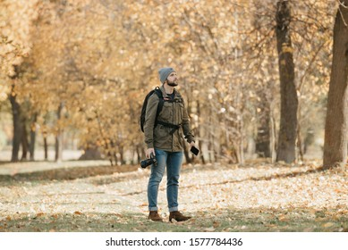A photographer with a beard in aviator sunglasses with mirror lenses, olive military combat jacket, jeans, hat with backpack and wristwatch holds the DSLR camera, the smartphone and waits