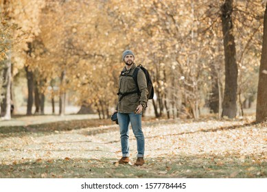 A photographer with a beard in aviator sunglasses with mirror lenses, olive military jacket, jeans, hat with backpack and wristwatch holds the DSLR camera and the smartphone in the forest at the noon
