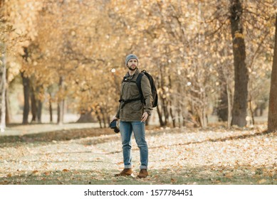 A photographer with a beard in aviator sunglasses with mirror lenses, olive military jacket, jeans, hat with backpack and wristwatch holds the DSLR camera and the smartphone in the forest.