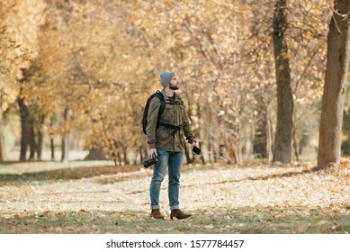 A photographer with a beard in aviator sunglasses with mirror lenses, olive military combat jacket, jeans, hat with backpack and wristwatch holds the DSLR camera and the smartphone in the forest