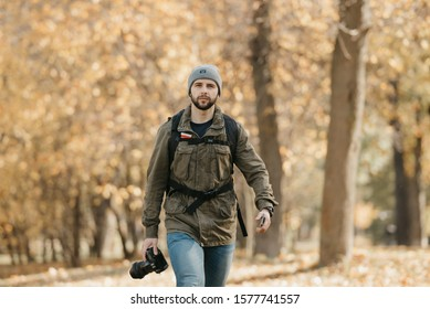 A photographer with a beard in aviator sunglasses, olive military combat jacket, jeans, hat with backpack and wristwatch holds the DSLR camera and the smartphone goes straight at the afternoon.