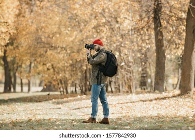 A photographer with a beard in an olive military cargo jacket, jeans, red hat with backpack and wristwatch takes photos with his professional DSLR camera in the forest at the noon
