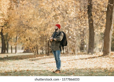 A photographer with a beard in olive military combat cargo jacket, jeans, red hat with backpack holds the DSLR camera and his wristwatch and looks away in the forest at the afternoon