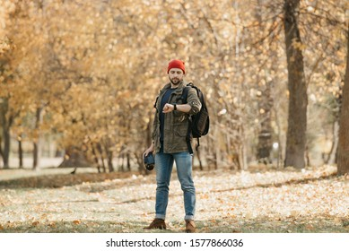 A photographer with a beard in olive military combat cargo jacket, jeans, red hat with backpack holds the DSLR camera checks the time on the wristwatch in the forest at the afternoon