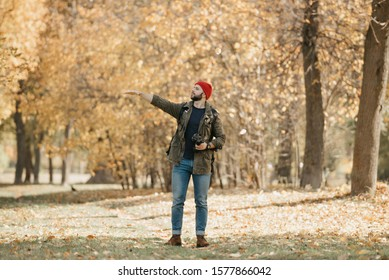 A photographer with a beard in olive military combat jacket, jeans, red hat with backpack and wristwatch holds the DSLR camera points a hand to the left in the forest at the afternoon