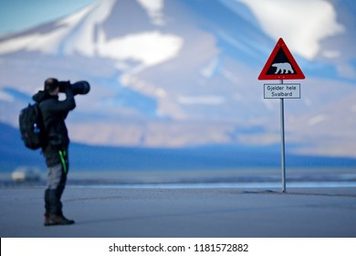 "Photographer with big lens and road traffic sign with Polar bear. ""Gjelder Hele Svalbard"" means ""Over All of Svalbard (watch out for polar bears)"". Man on the road with snowy mountain, Svalbard."