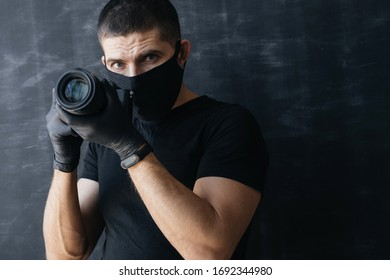 Photographer in a black mask, a T-shirt and gloves, holds the camera in his hands on a dark background. Concept Photo business and coronovirus.