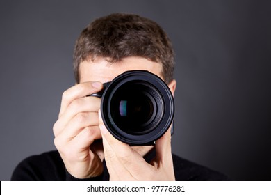 Photographer with a camera, focus is on the lens