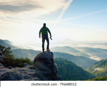 Photographer with camera in hand on top of mountain. Hiker climbed on peak of rock above foggy valley. Man watch over misty and foggy morning valley to bright morning Sun.