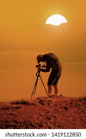 photographer with camera on tripod taking landscape pictures from mountain peak at sunset