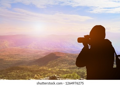 Photographer with camera. white mist Beautiful morning sun. There are mountains