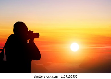 Photographer with camera.white mist.Beautiful morning sun.There are mountains alternating.Branches of pines.