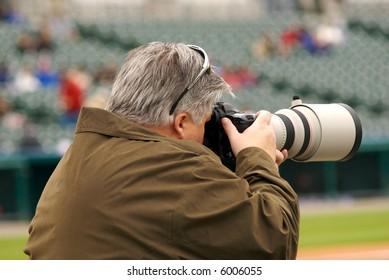 A photographer capturing an image at a baseball game.