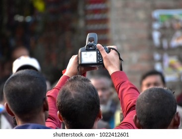 Photographer is capturing a photo standing among the crowd stock photograph