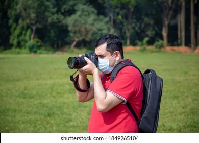 Photographer capturing photos during Coronavirus disease (COVID-2019) pandemic wearing face mask