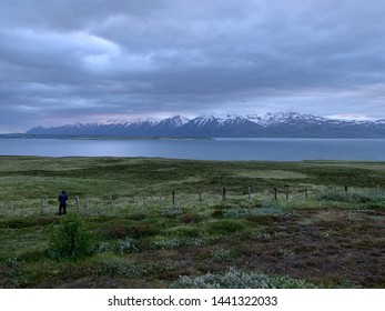 Photographer capturing the rugged and isolated landscape of northern Iceland. View across a fjord with snow capped mountains in the distance. Green field with fence.