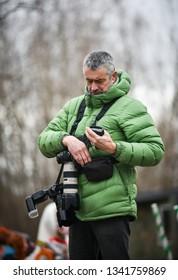 Photographer checks the settings of camera outdoors. Rezekne - Latvia, March 2019
