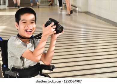 Photographer child on wheelchair is holding a camera in hand. He was smiling and having fun with it.