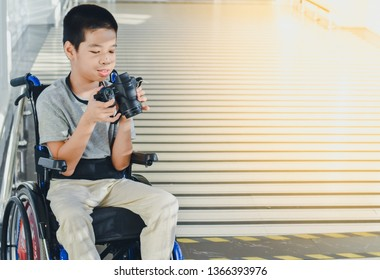 Photographer child on wheelchair is holding a camera in hand, He was smiling and having fun with it,Life in the education age of disabled children, Happy disabled kid concept.