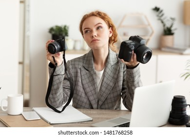 Photographer choosing photocamera for shooting, having doubts, working in office on laptop