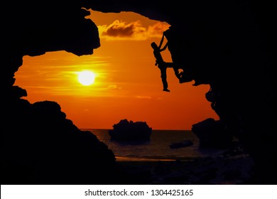 Photographer climbing rock in the cave near the beach with kayaking and red sky sunset.