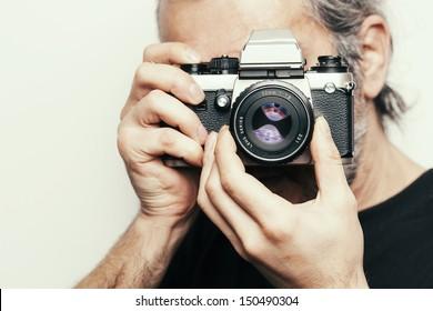 Photographer. Close up portrait of man holding vintage camera.