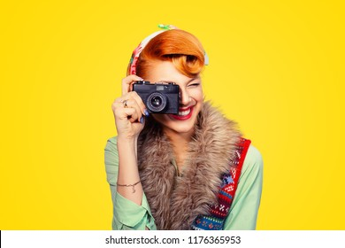Photographer. Closeup portrait head shot young woman lady pinup girl taking pictures with dslr camera, retro, vintage hairstyle isolated yellow background. Wedding travel photography hobby paparazzi