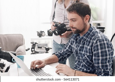 Photographer and designer working together at the creative agency, the woman is holding a camera and the man is connecting with a laptop