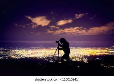 Photographer with dreadlocks in silhouette taking shot with camera on tripod against night sky with stars and glowing city light background.