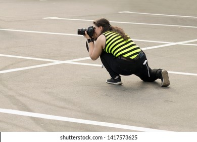 A photographer with DSLR camera is taking pictures of someone in the parking lot. Moscow - June 1, 2019. Hidden photographing, paparazzi concept