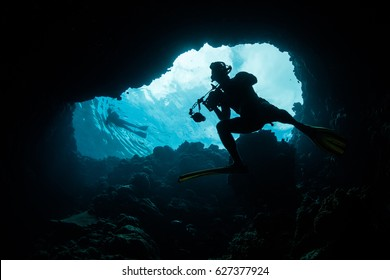 A photographer explores a blue hole in the Republic of Palau. Dark holes, caverns, and caves serve as habitat for many fish and invertebrates that shun sunlight.