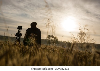 Photographer or filmmaker early in the morning honing his craft. Going that extra mile for a good shot.