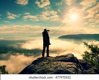 Photographer with folded  tripod on cliff shadowing eyes and thinking. Heavy fogy landscape, misty sunrise in  beautiful valley below