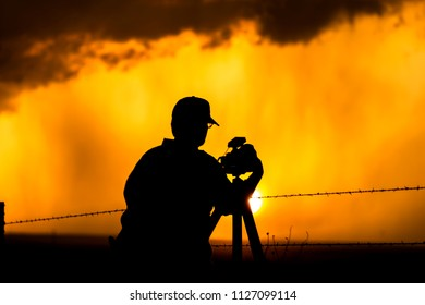 A photographer is framed against a thunderstorm sunset while rain pours in the distant orange and yellow hue.