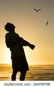 Photographer gazing skyward to photograph birds at sunset