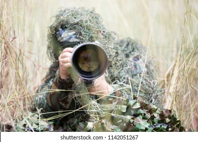 Photographer in ghillie suit hiding in forest to take wildlife photo for education