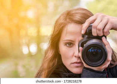 photographer girl, close-up portrait. The girl model takes photos, looking at the viewer and into the lens of the outdoor camera. copyspace