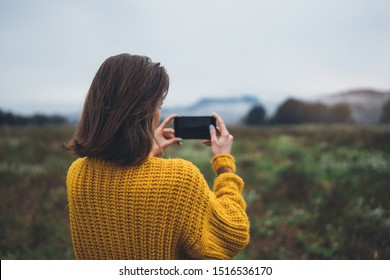 photographer girl hold in hands mobile phone taking photo on smartphone autumn foggy mountain, tourist shooting on photo camera on background landscape