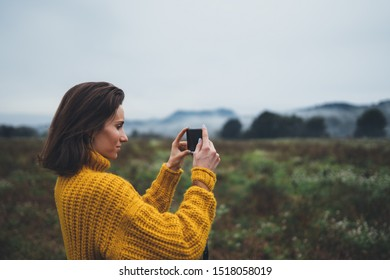 photographer girl hold in hands mobile phone taking photo on smartphone autumn foggy mountain, tourist shooting on photo camera on background landscape, internet online concept