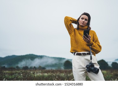 photographer girl hold in hands mobile typing message on smartphone on background landscape autumn foggy mountain, tourist shoot on photo camera using internet online gadget, hobby concept