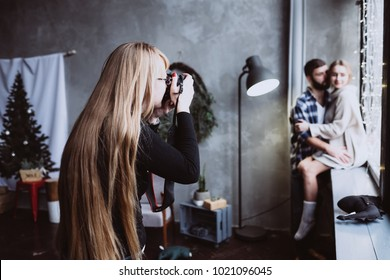 Photographer girl with long blondie hair take picture of a young romantic couple in love at cozy home