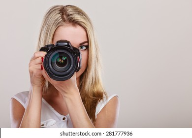 Photographer girl shooting images. Attractive blonde woman taking photos with camera.