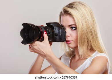 Photographer girl shooting images. Attractive blonde woman taking photo with camera.