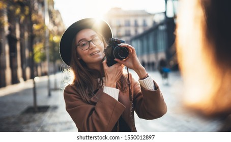 Photographer in glasses with retro camera take photo girlfriend. Tourist smiling girl in hat travels in Barcelona holiday with friend. Sun flare street in europe city. Traveler hipster shoot girls