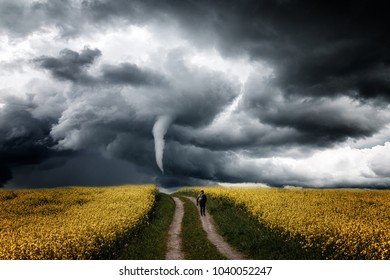 Photographer goes across the field towards storm