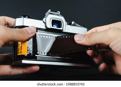 Photographer hand loading 35mm film into SLR film camera.