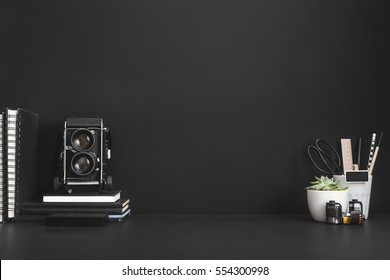 Photographer or hipster workspace. Black background with medium format camera, notebooks, etc.